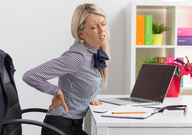 Woman having back pain while sitting at desk in office